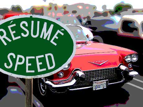 a resume speed sign in front of a classic cadillac